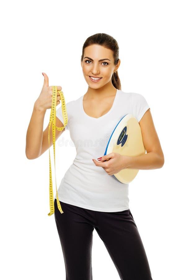 Junge brunette Frau in den weißen T-Shirt Griffskalen und -band gibt Daumen auf Stände, die das Lächeln auf weißem Hintergrund au stockfotos