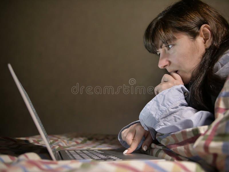 Junge brunette Frau, die auf dem Bett liegt und in ihrem Laptop arbeitet lizenzfreie stockfotos
