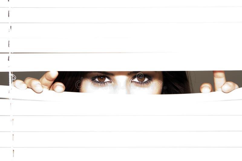 Junge Brunette-Frau, die durch die Vorhänge schaut lizenzfreie stockfotos