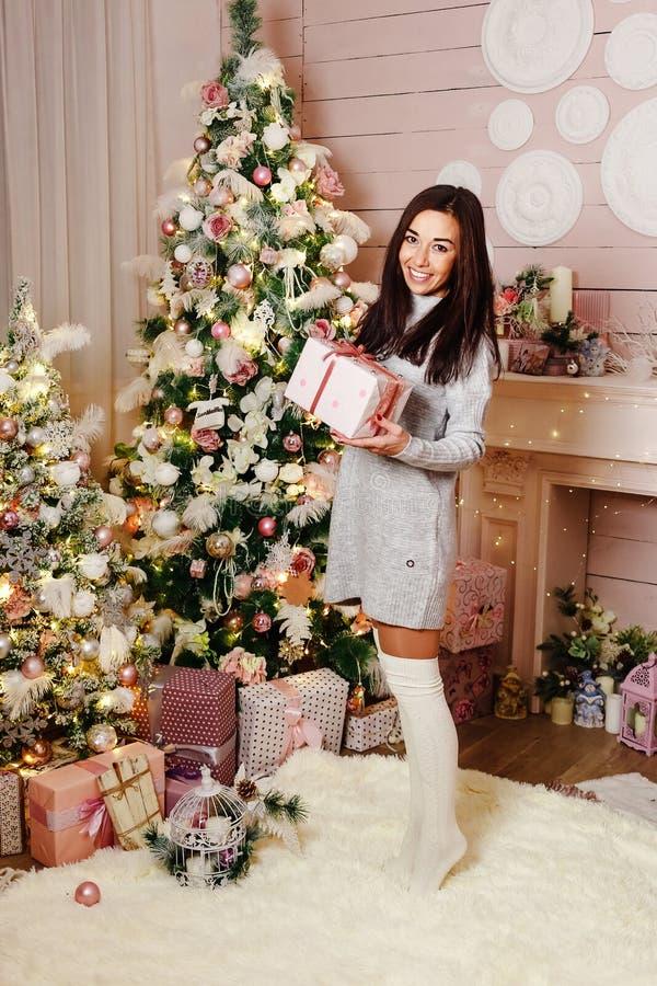 Junge brunette Frau, die mit dem Weihnachtsgeschenk nahe Weihnachtsbaum lächelt lizenzfreies stockfoto