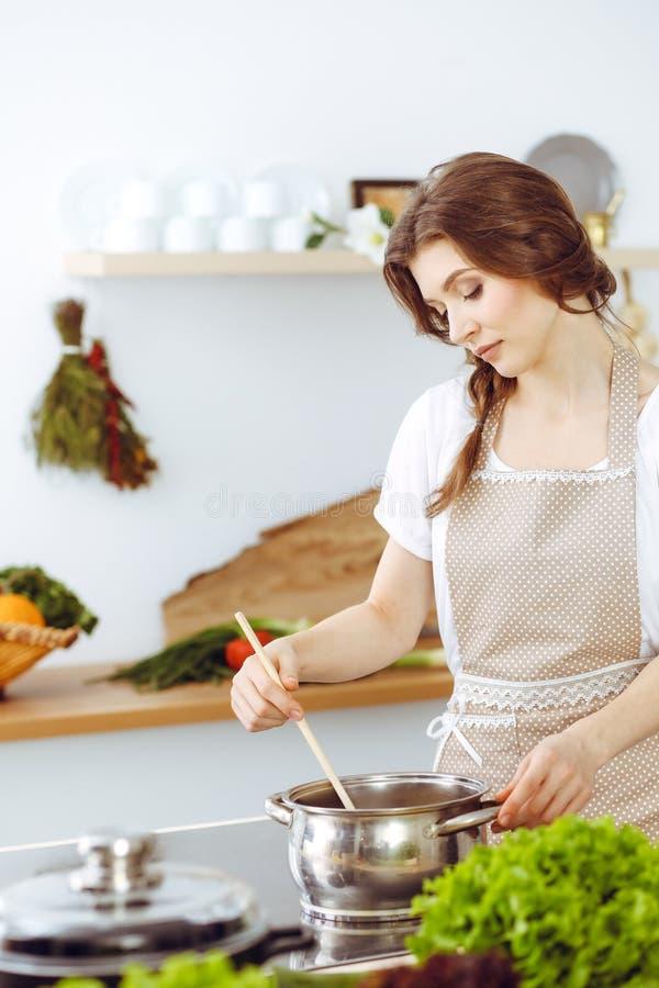 Junge brunette Frau, die Suppe in der K?che kocht Hausfrau, die h?lzernen L?ffel in ihrer Hand h?lt Lebensmittel und Gesundheitsk lizenzfreie stockbilder