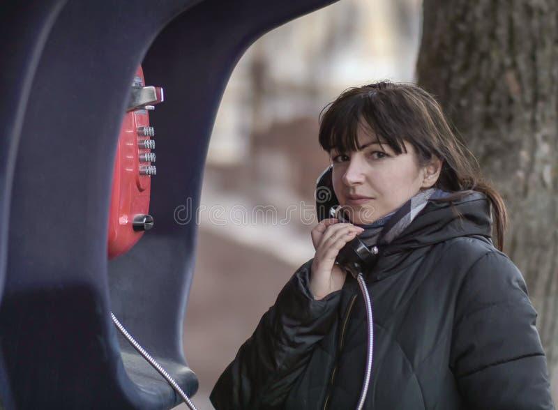 Junge brunette Frau, die von einem roten Straßenmünztelefon, betrachtend direkt der Kamera nennt stockbilder