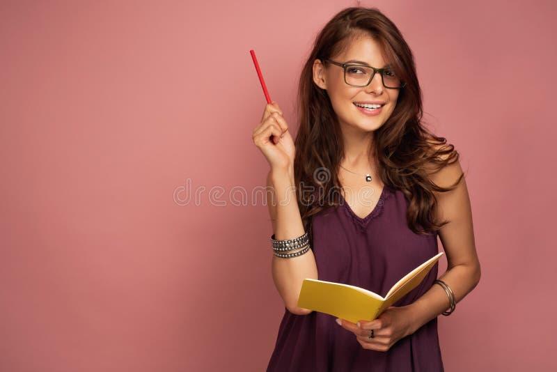 Junge brunette Frau hält Stift in einer Hand und im gelben Notizbuch in anderer Hand, welche die Kamera durch Brillen betrachtet lizenzfreie stockfotografie