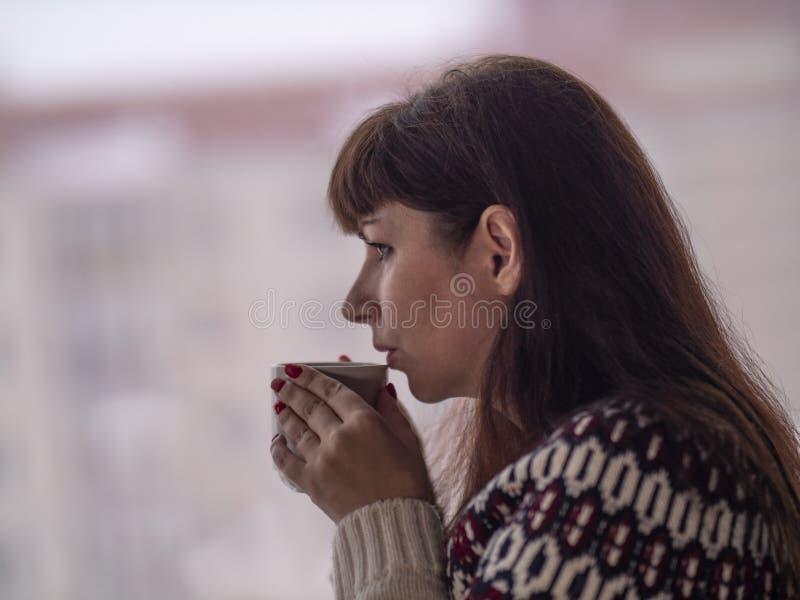 Junge brunette Frau trinkt Kaffee und schaut heraus das Fenster durchdacht stockfoto