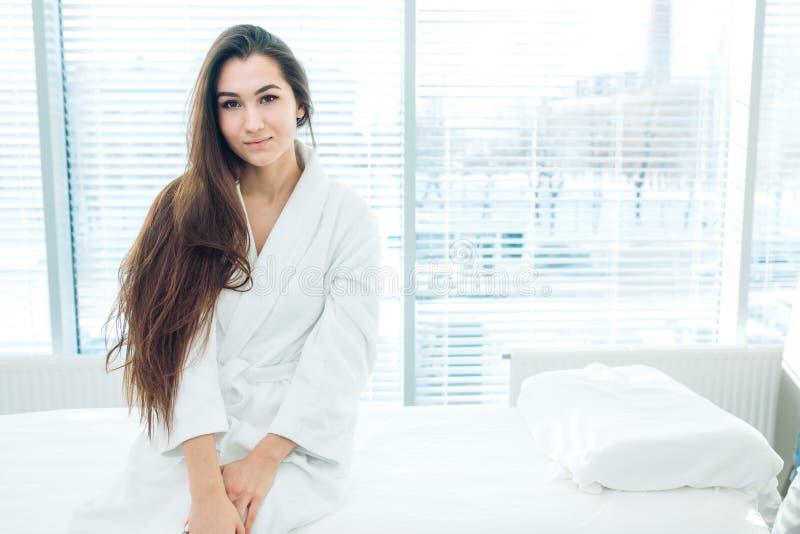 Junge brunette Frau in weißer Bademantel Warte-LPG-Massagesitzung stockfotografie