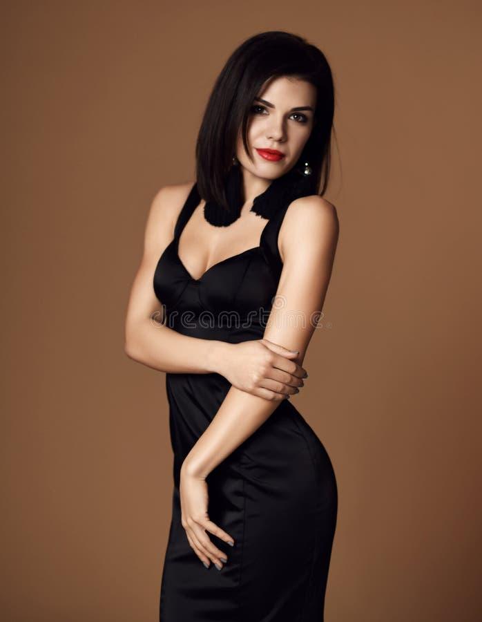 Junge brunette sexy Modefrau, die in der kleinen Schwarze auf Beige aufwirft lizenzfreies stockfoto