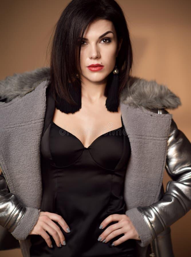 Junge brunette sexy Modefrau, die im grauen Pelzmantel und in der schwarzen legeren Kleidung auf Beige aufwirft lizenzfreies stockfoto
