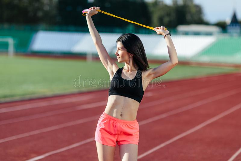 Junge brunette Sportlerin mit einer perfekten Zahl auf sportlicher Lebensstilstellung des Stadions auf der Bahn, die mit Seilspri stockfotos
