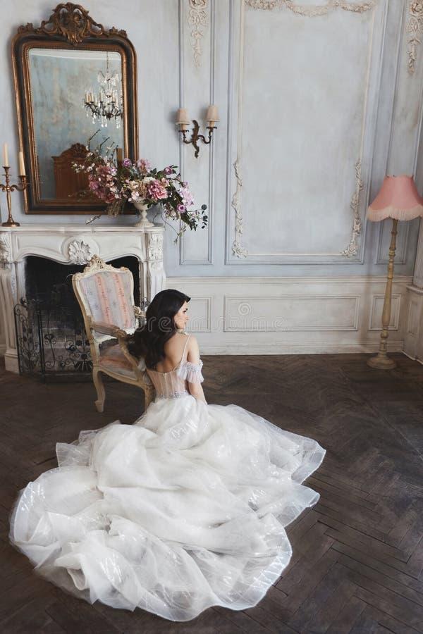Junge brunette vorbildliche Frau in einem stilvollen Spitzehochzeitskleid mit nackten Schultern sitzt auf dem Boden nahe dem Kami stockbilder