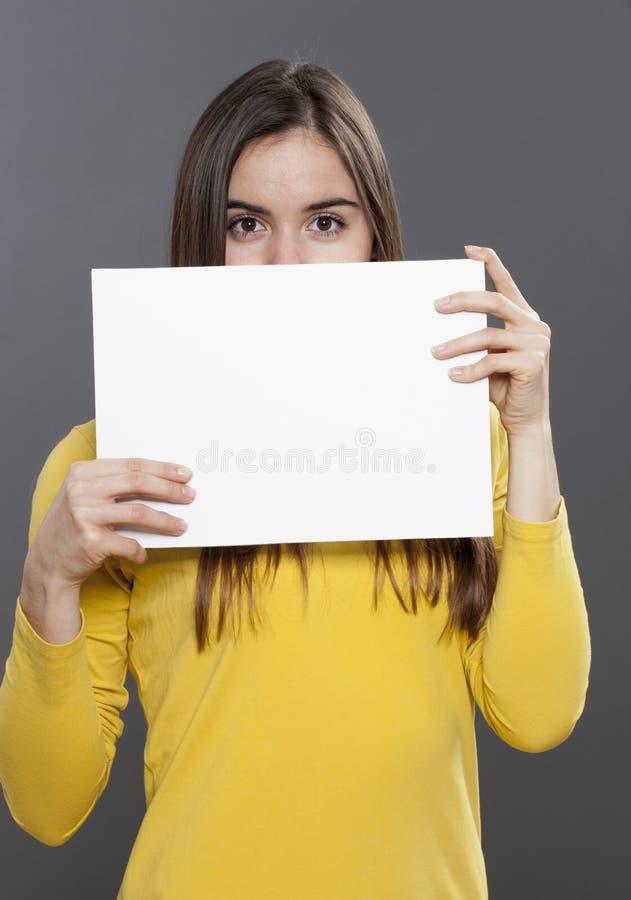 Junge Brunettedame, die Darstellungskarte hält lizenzfreie stockbilder