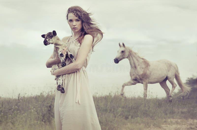 Junge Brunettedame, die kleines Lamm hält stockfoto