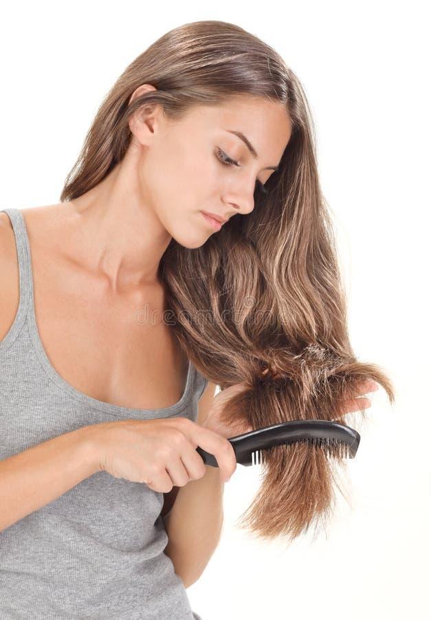 Junge Brunettedame, die lange Haare kämmt lizenzfreie stockbilder