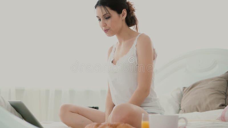 Junge Brunettefrau dehnt zu Hause auf ein Bett aus Schönes Mädchen, das Laptop verwendet, um während des Frühstücks anzuschließen lizenzfreies stockbild