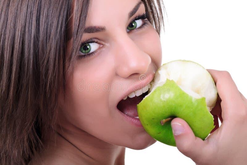 Junge Brunettefrau, die Äpfel isst stockfotos