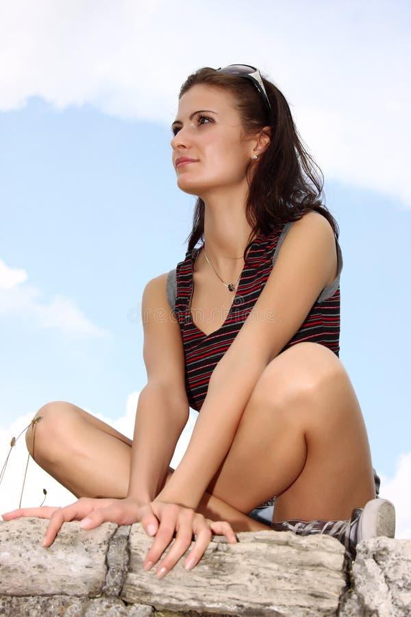 Junge Brunettefrau, die auf einem Felsen sitzt stockbild