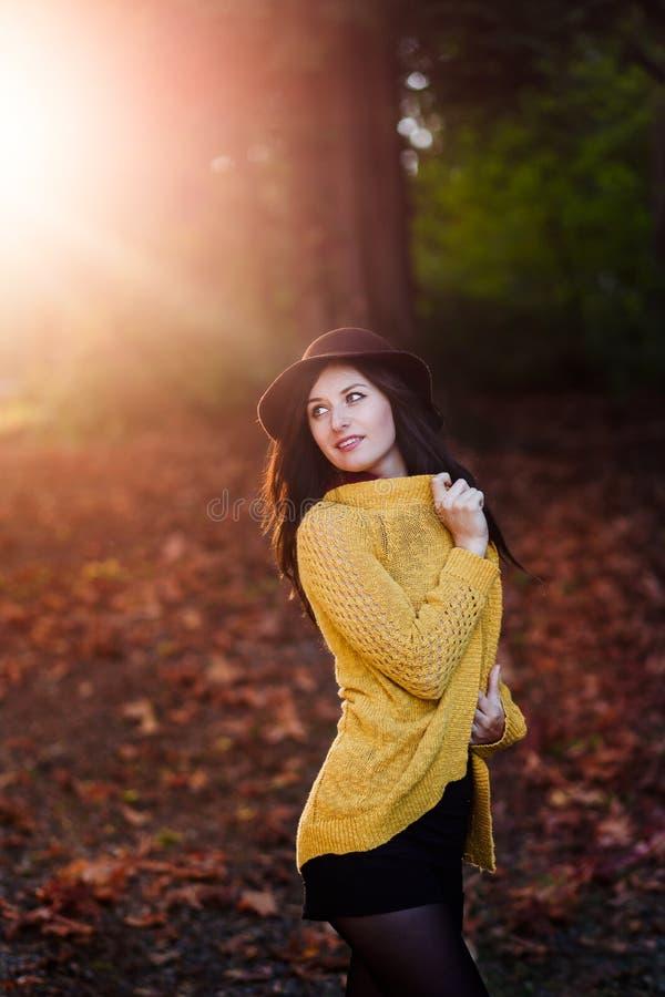 Junge Brunettefrau, die auf einem hölzernen Weinfaß vor einem Okanagan-Weinberg sitzt stockbild