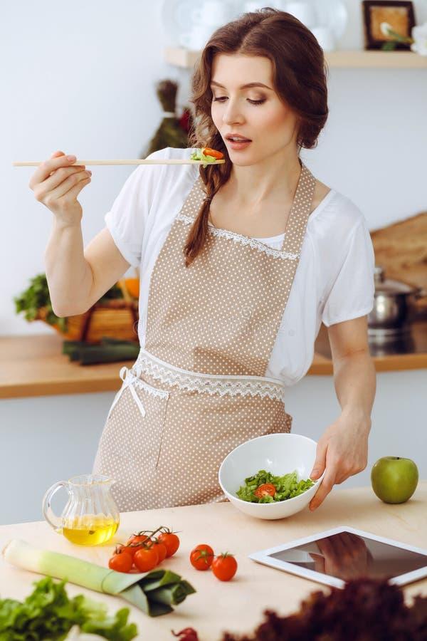 Junge Brunettefrau, die in der K?che kocht Hausfrau, die h?lzernen L?ffel in ihrer Hand h?lt Lebensmittel und Gesundheitskonzept lizenzfreie stockfotografie