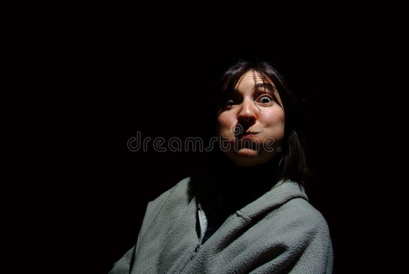 Junge Brunettefrau, die heraus ihre Backen über schwarzem backgroun durchbrennt stockfotos