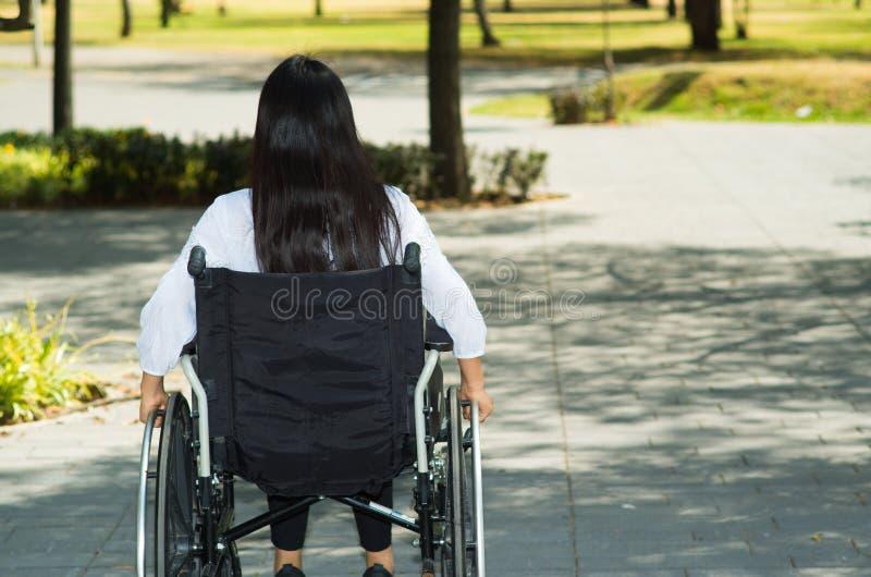 Junge Brunettefrau, die im Rollstuhl lächelt mit positiver Haltung, draußen Umwelt, körperliche Wiederaufnahme sitzt stockfotos