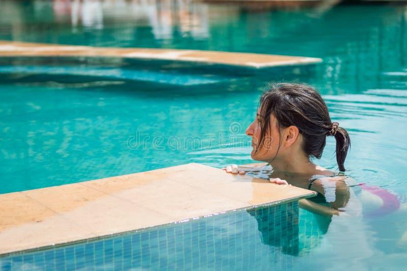 Junge Brunettefrau, die im Swimmingpool in einem Erholungsort sich entspannt lizenzfreie stockbilder