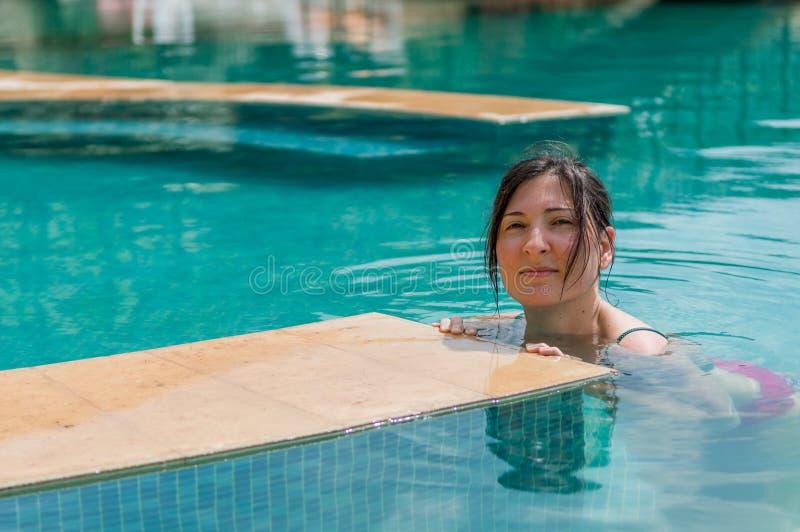 Junge Brunettefrau, die im Swimmingpool in einem Erholungsort sich entspannt stockfoto