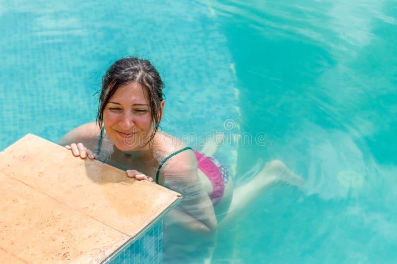 Junge Brunettefrau, die im Swimmingpool in einem Erholungsort sich entspannt stockfotografie