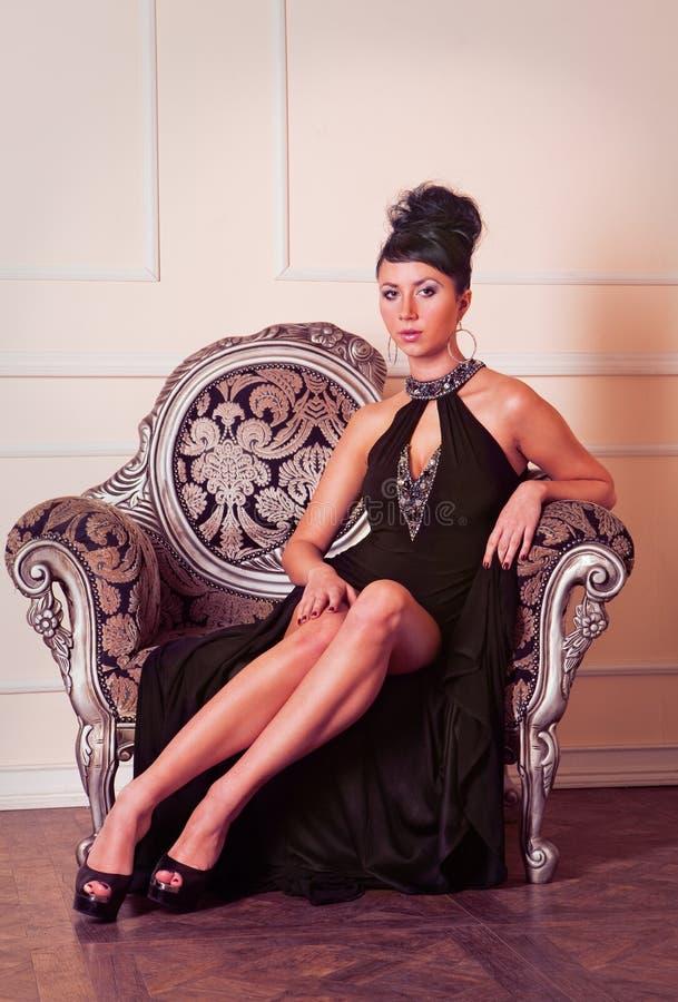Junge Brunettefrau im schwarzen Kleidsitzen stockbild