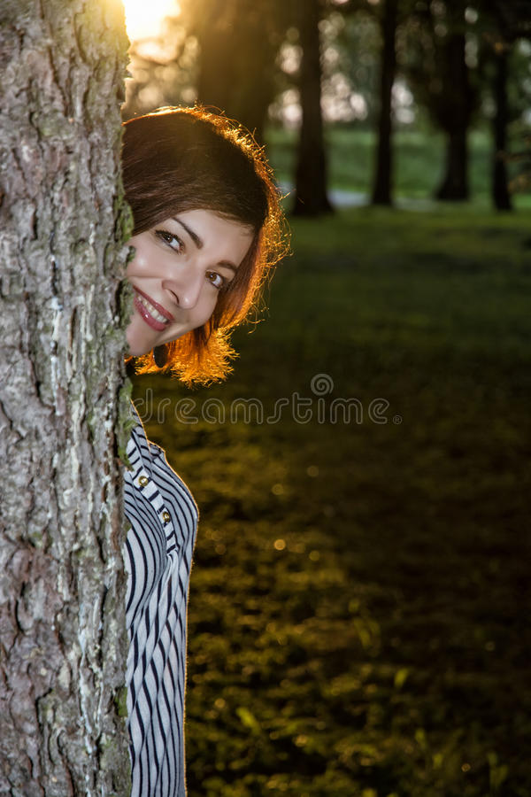 Junge Brunettefrau knallt heraus hinter dem Baum durch Sonnenuntergang lizenzfreie stockfotografie