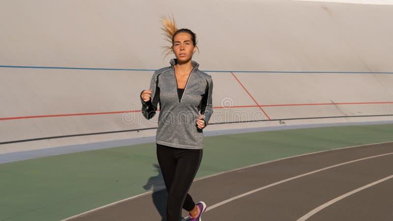 Junge Brunettefrau läuft morgens auf Sportbahn lizenzfreies stockfoto