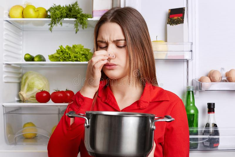 Junge Brunettefrau mit missfallenem Ausdruck riecht verdorbene Suppe in der Eintopfgerichtwanne, glaubt schaler Küche des Geruchs stockbilder