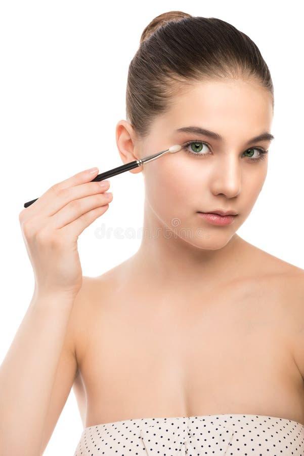 Junge Brunettefrau mit sauberem Gesicht Perfekte Haut des Mädchens, die kosmetische Bürste anwendet Getrennt auf einem Weiß stockbild