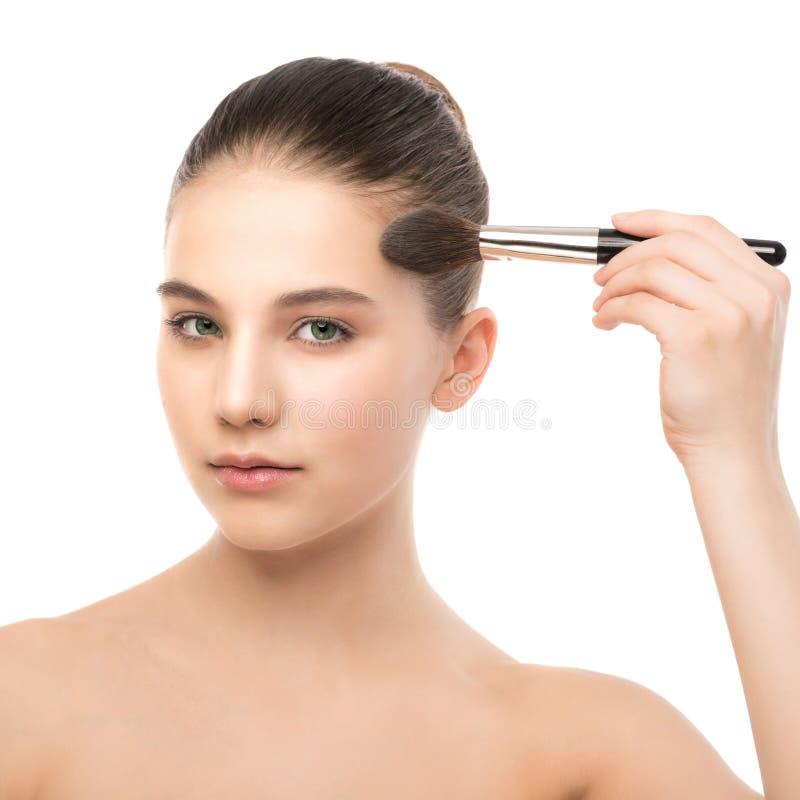 Junge Brunettefrau mit sauberem Gesicht Perfekte Haut des Mädchens, die kosmetische Bürste anwendet Getrennt auf einem Weiß stockfoto