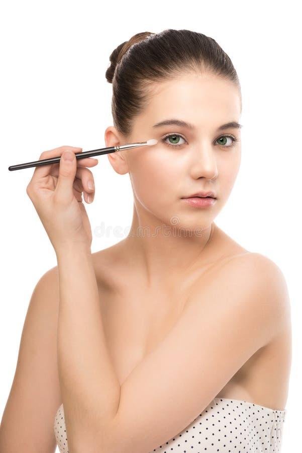 Junge Brunettefrau mit sauberem Gesicht Perfekte Haut des Mädchens, die kosmetische Bürste anwendet Getrennt auf einem Weiß lizenzfreie stockfotos