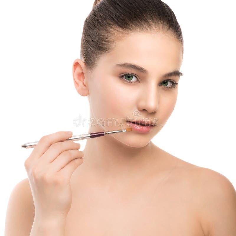Junge Brunettefrau mit sauberem Gesicht Perfekte Haut des Mädchens, die kosmetische Bürste anwendet Getrennt auf einem Weiß stockbilder