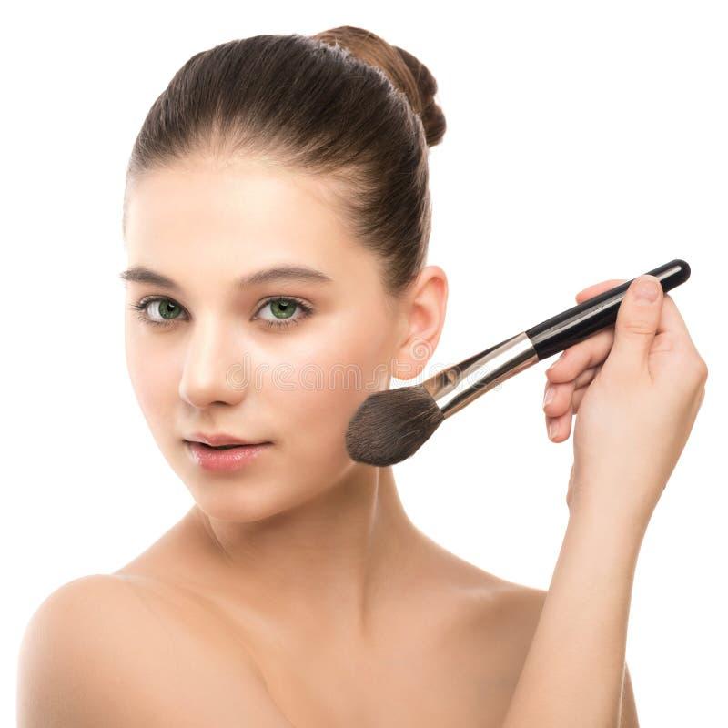 Junge Brunettefrau mit sauberem Gesicht Perfekte Haut des Mädchens, die kosmetische Bürste anwendet Getrennt auf einem Weiß stockfotografie