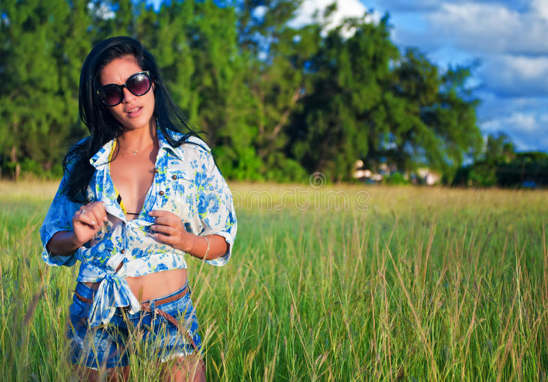 Junge Brunettefrau mit Sonnenbrille auf grüner Rasenfläche lizenzfreies stockfoto