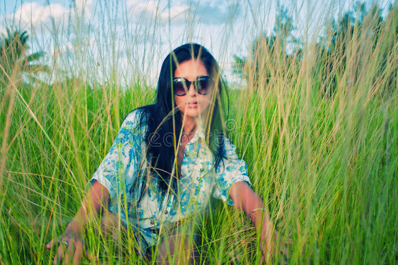 Junge Brunettefrau mit Sonnenbrille auf grüner Rasenfläche lizenzfreie stockbilder
