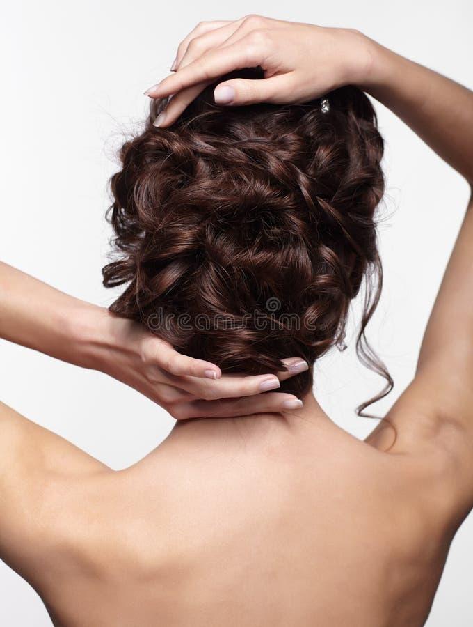 Junge Brunettefrau von der Rückseite mit Knoten umsponnenem Haar stockfoto
