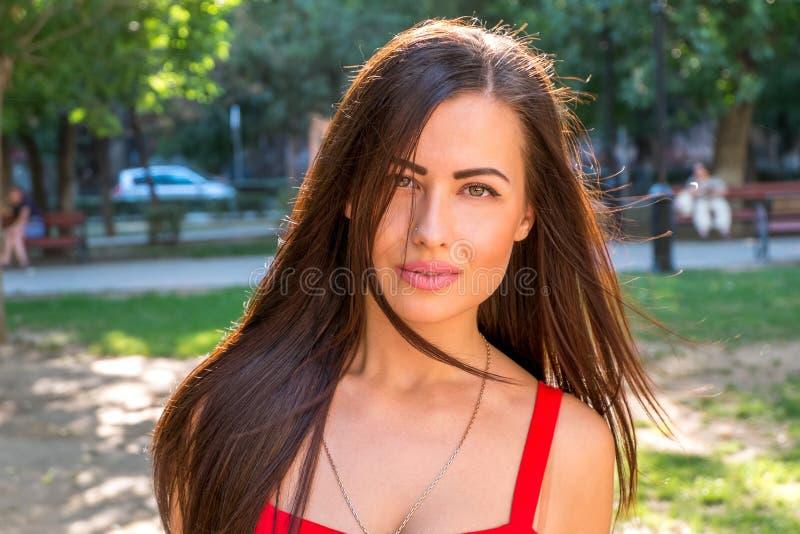 Junge Brunettefrauen draußen löschen Ausdruck auf ihrem hübschen Gesicht lizenzfreie stockfotos