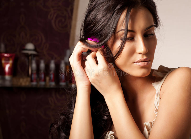 Junge Brunettefrauen-Festlegungblume im lockigen Haar stockbild