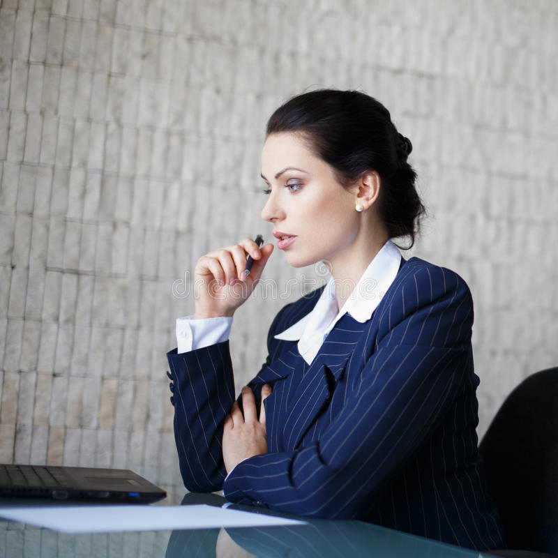 Junge Brunettegeschäftsfrau, die im Büro denkt stockfotografie