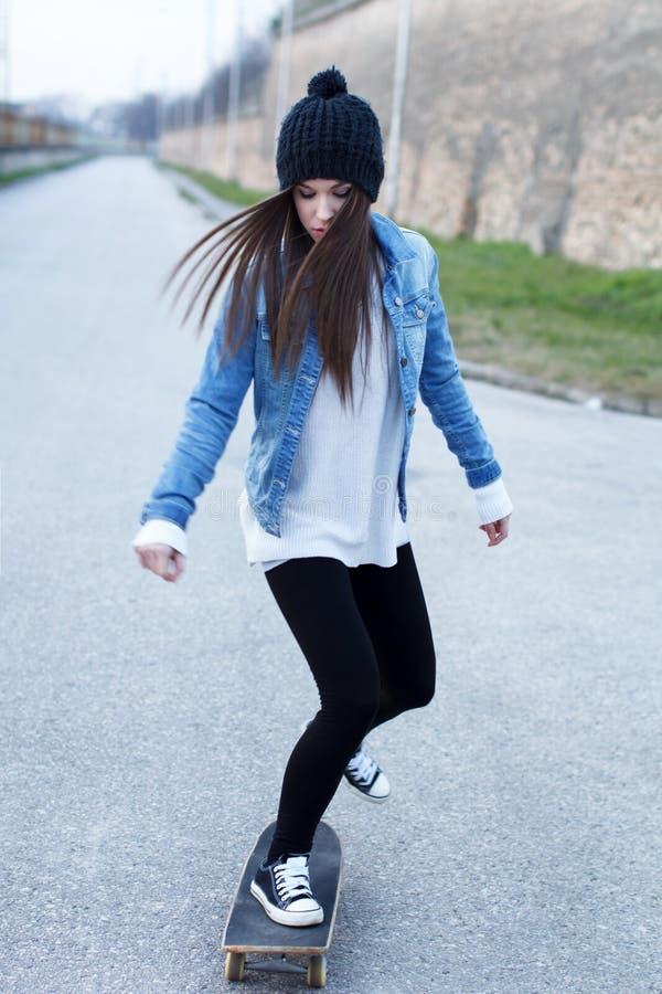 Junge Brunetteskateboardfahrer-Mädchenpraxis lizenzfreie stockfotos