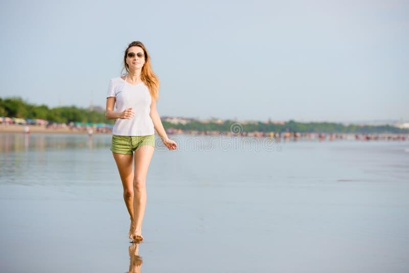 Junge caucasion Frau, die auf dem Strand an läuft lizenzfreie stockfotos