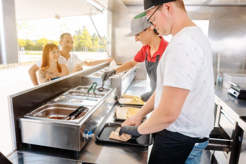 Junge Chefs in einem Nahrungsmittel-LKW, der Nahrung für ihre Wartekunden zubereitet stockfotografie