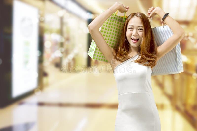 Junge chinesische Frau, die viele Einkaufstaschen auf dem Mall hält stockbild