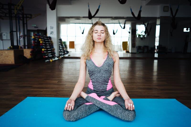 Junge dünne blonde Frau in der Yogaklasse stockfotos