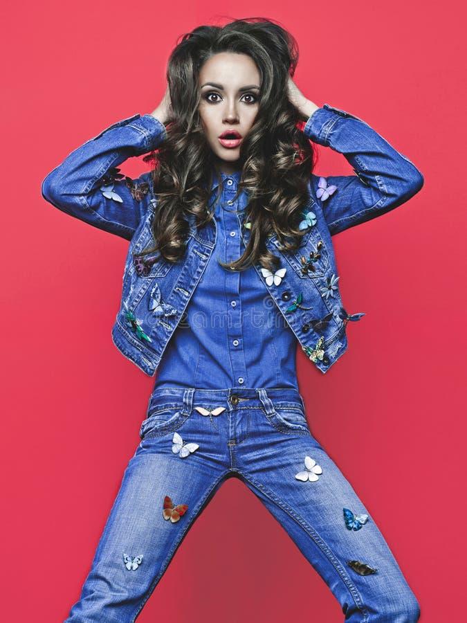 Junge dünne Frau in den Jeans mit vielen Broschen lizenzfreie stockfotos