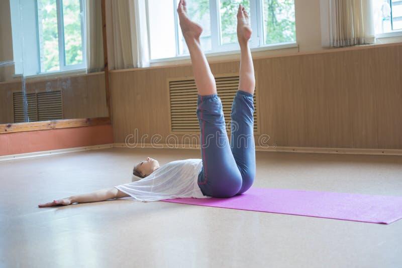 Junge dünne Frau mit dem blonden Haar, das auf dem Boden mit ihren Beinen oben liegt stockfotos