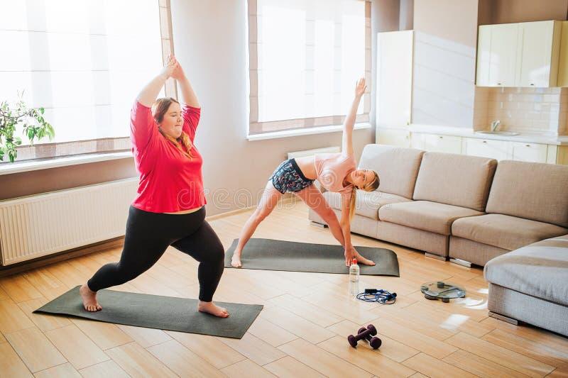 Junge dünne und überladene Modelle, die zusammen im Wohnzimmer exersicing sind Stellung in asana oder Yogahaltungen Training f?r  lizenzfreies stockbild