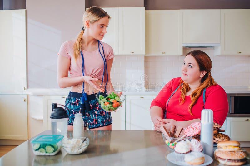Junge dünne und fette Frauen in der Küche betrachten einander Gut gebaut vorbildliche Griffschüssel mit Salat Überladener vorbild lizenzfreie stockfotografie